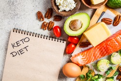 Keto diet food concept. Fish, eggs, cheese, nuts, butter and vegetables - ingredients keto diet, top view.