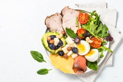 Keto diet plate. Low carb dish, healthy nutrition. Baked meat, eggs, avocado, salad leaves, cheese and fish. Top view.