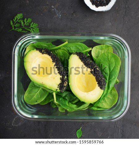 Keto paleo diet ingredients. Avocado spinach lunch box. Allowed fresh green vegetables, leafy greens for low-carb diets, maximum fiber and healthy fats. In a glass box. On a dark background. Top view.
