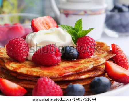Keto pancakes made of coconut flour or almond flour, served with berries and whipped cream
