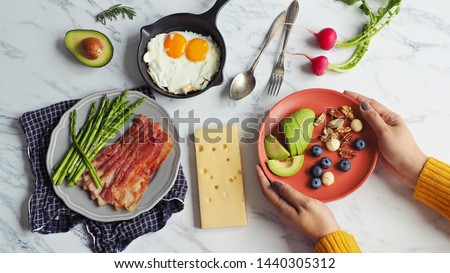 Ketogenic diet meal preparation female hands serving red plate with avocado, blueberry, Brazil nut, macadamia, pecan, walnut on marble table with fried eggs, bacon, roasted asparagus and cheese.