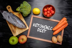 Ketogenic Diet (or Keto Diet) on chalkboard, health conceptual. Healthy fresh low carbohydrates food; egg, fish, lemon, tomatoes, apple, carrot and broccoli.
