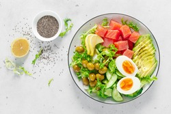 Ketogenic, keto or paleo diet lunch bowl with salted salmon fish, lemon, avocado, olives, boiled egg, cucumber, green lettuce salad and chia seeds. Healthy food trend. Top view