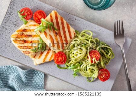 ketogenic paleo diet lunch. halloumi cheese, spiralized zucchini with arugula pesto and tomatoes #1565221135
