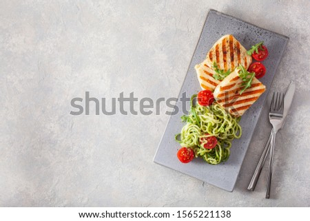ketogenic paleo diet lunch. halloumi cheese, spiralized zucchini with arugula pesto and tomatoes #1565221138