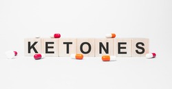 KETONES the word on wooden cubes, cubes stand on a reflective white surface. Medicine concept