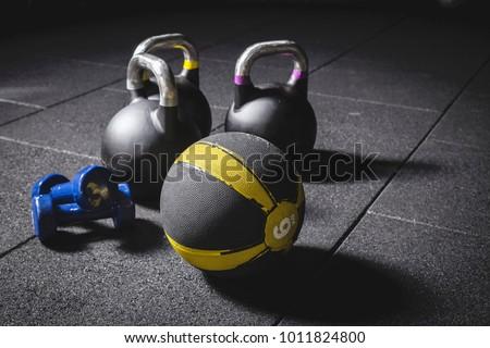 Kettle bells, medicine ball and dumbbells on the black gym floor, fitness equipment