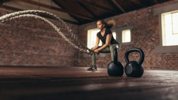 Kettle bells on floor in front and woman exercising with battle rope. Female exercising at cross training gym.