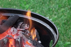 Kettle Grill Pit With Flaming Charcoal. BBQ Hot Grill Close Up. Barbecue Kettle Grill On The Summer Backyard Ready For Grilling Cookout Food.