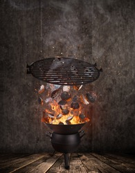 Kettle grill with hot briquettes and cost iron grid flying in the air. Freeze motion barbecue concept.