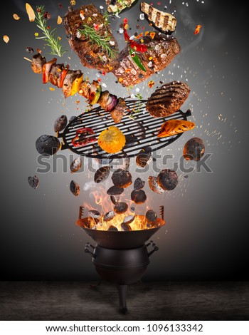 Kettle grill with hot briquettes, cast iron grate and tasty skewers flying in the air. Freeze motion barbecue concept.
