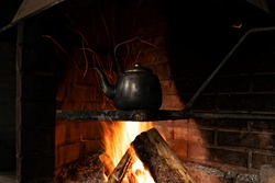 Kettle on the fire. Cooking in nature during a hike. Sparks.