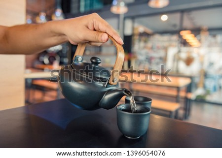 Kettle pouring boiling water into a cup during coffee time in coffee shop #1396054076