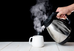kettle pouring boiling water into a cup with smoke on wood table
