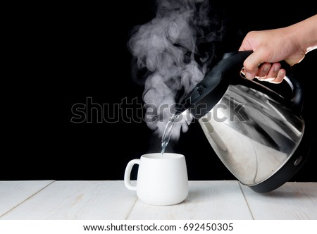 kettle pouring boiling water into a cup with smoke on wood table Stock photo ©