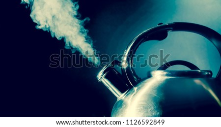Kettle whistling, boiling kettle with steam texture on a black background. Vintage, grunge old retro style photo.