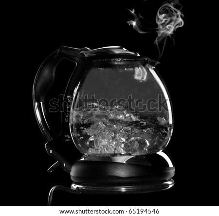Kettle with boiling water and steam isolated with clipping path on black background