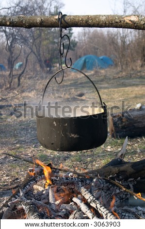 Kettle with food above the fire in the camping