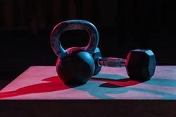 Kettlebell and dumbbell in red-blue gradient light on dark background