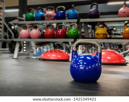 Kettlebell at a gym with more colorful kettlebells on the background with copy space