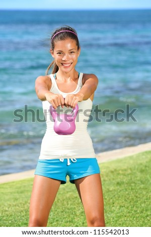 Kettlebell fitness woman exercising outside lifting kettlebells. Beautiful young fit fitness model smiling happy.