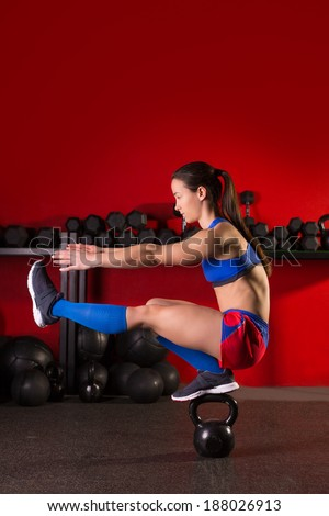 kettlebell woman pistol squat workout balance in red gym - stock photo