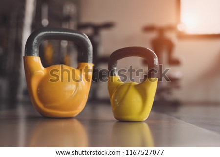 Kettlebells or dumbbells on fitness gym floor. Heavy weight sports equipment and accessories in workouts training club. Body building muscle and strength weightlifting. Lifestyle and indoors activity. #1167527077