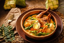Ketupat Lebaran. Eid celebratory dish of rice cake with Ayam Opor Bakar (grilled chicken curry), Sayur Lodeh (spicy vegetable curry soup) and Semur Tahu Telur (braised bean curd and egg in soy sauce).