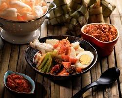 Ketupat Lebaran. Traditional Celebratory Dish of Rice Cake with Several Side Dishes, Popular Served during Eid al Fitr Celebrations. Served with Sambal Goreng Ati, Opor Ayam, Kerupuk, and Sambal.