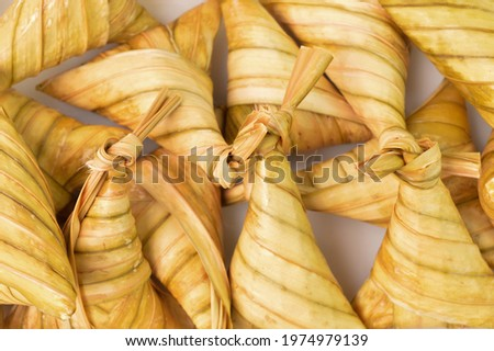 Ketupat palas or rice dumpling in a white plate. Ketupat palas is a natural rice casing made from young coconut leaves or cooking rice during Eid Mubarak or Eid Fitri Foto stock ©