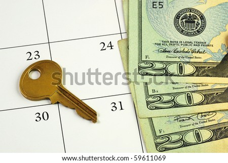 Key and money on a calendar concepts of paying the mortgage on time