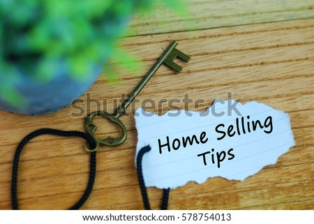 Key and torn paper with text home selling tips on wooden background