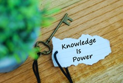Key and torn paper with text knowledge is power on wooden background