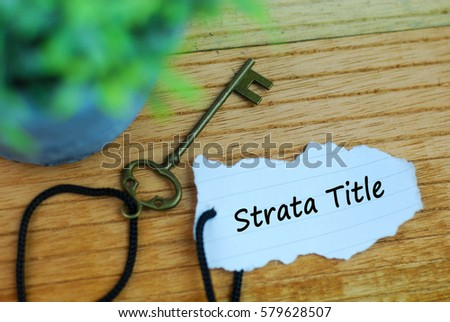 Key and torn paper with text strata title on wooden background #579628507