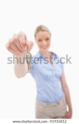 Key being handed over by woman against a white background