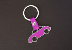 Key chain pink car on dark brown leather pad