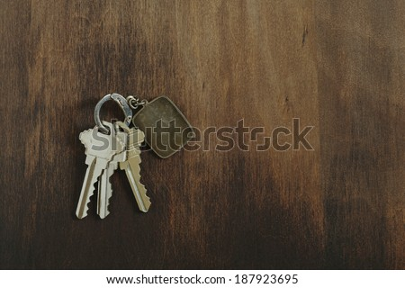 Key chain with three house or door keys on a dark wood table top.
