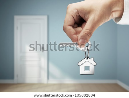 key in hand against the backdrop of the blue rooms