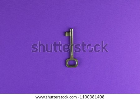 Key on a purple background, top view. Trendy colorful photo. Minimal style with colorful paper backdrop. Flat lay fashion concept: key on pastel background. Trendy minimal flat lay concept.
