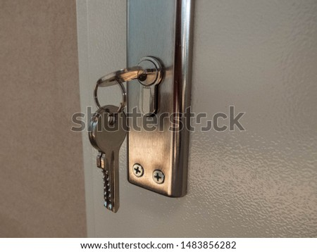 Key on the key chain inside the door keyhole #1483856282