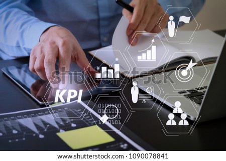 Key Performance Indicator (KPI) workinng with Business Intelligence (BI) metrics to measure achievement and planned target.businessman working with smart phone and digital tablet and laptop computer.
