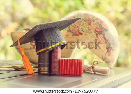 Key success in graduate study abroad program and open or expand world view experience concept : Graduation cap or hat, certificate or diploma, mini text books on a laptop computer, a half world globe.