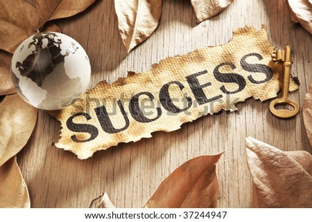 Key to global success concept using printed word on burnt paper along with compass and golden key, surrounded by dry leaf