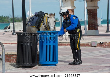 KEY WEST, FLORIDA - DEC 1: Policeman cares for his horse in Key West on December 1, 2011. Key West's Police Department is a full-service agency servicing over 25,000 residents and 6 square miles.