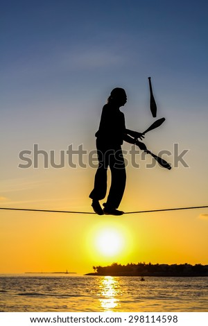Key West, Florida, United States - April 13, 2012: A tightrope walker tosses of skittles. Show of street artists that takes place every day at sunset
