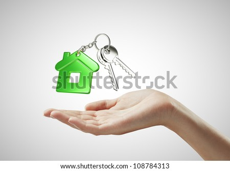 key with  green key chain in hand on white background