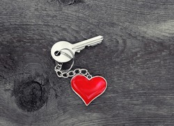 key with heart charm on old wooden table