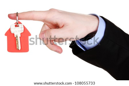 Key with house-shaped charm in hand isolated on white