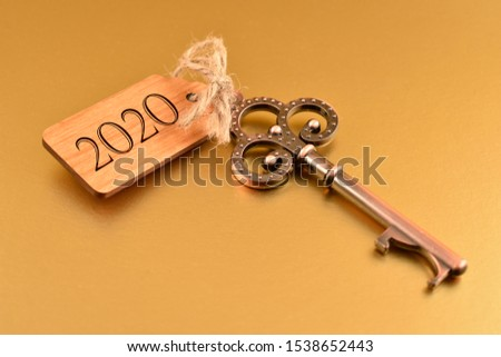 Key with number 2020 images. Old key with wooden tag. Decorated key isolated on a golden background. Romantic key with wooden label. Golden New Year 2020