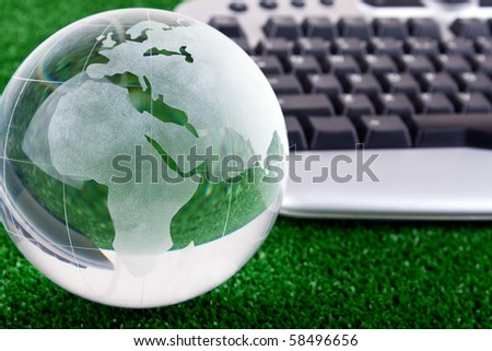 keyboard and glass globe on green grass